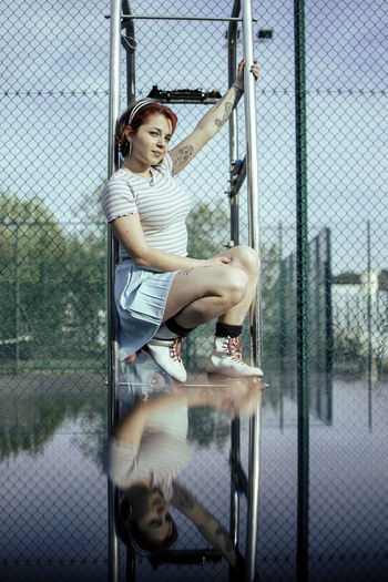 Portrait of woman sitting by chainlink fence