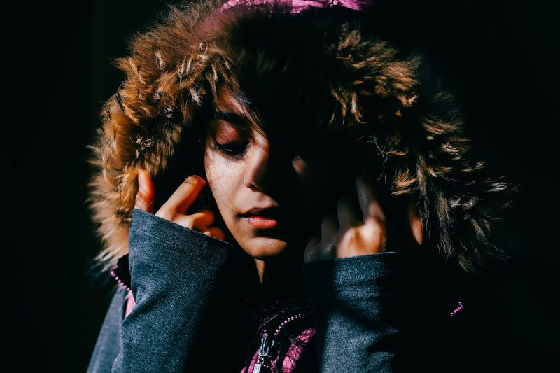 Close-Up Of Woman With Fur Hood Against Black Background