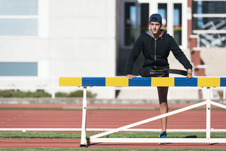 Man with prosthetic leg standing on running track