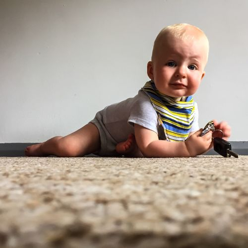 Portrait Of Cute Baby Holding Key At Home