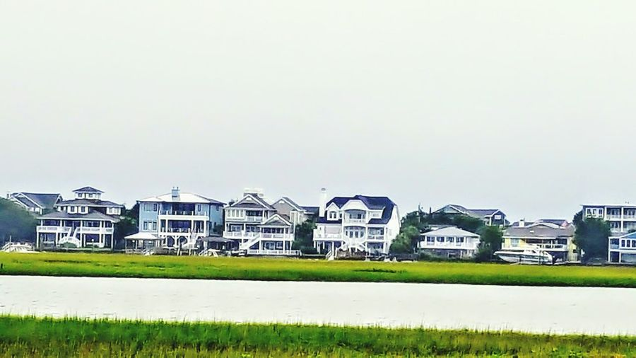 Building Exterior Grass Built Structure Architecture Residential Building Day Outdoors City Sky No People Cityscape Wrightsville Beach NC Wrightsville Beach Tranquility Sea Water Cloud - Sky Power In Nature Abstract Architecture Horizon Over Water Sea Life Wet Landscape