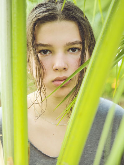 Close-up portrait of girl by plants