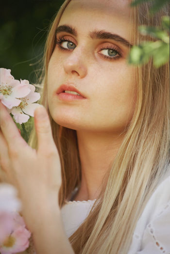 Close-up portrait of beautiful woman holding flower outdoors