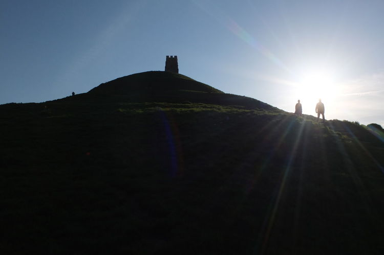 Climbing Glastonbury Tor on a clear evening English Countryside Historical Building Sacred Places Silhouette St Michaels Chapel Architecture Beauty In Nature Evening Glastonbury Tor History Lens Flare Low Angle View Sacred Site Sky Sunbeam Sunlight Sunset Tourism Travel Destinations Two People