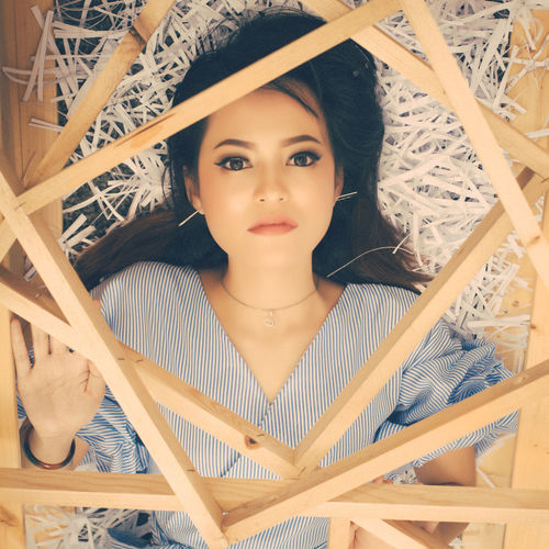 Directly above view of beautiful woman lying on paper with wooden picture frames