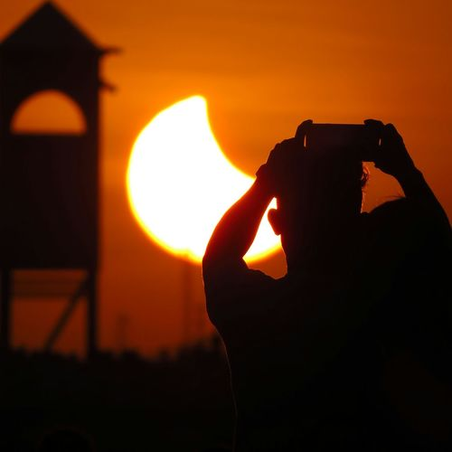 All registering the eclipse. CEARÁ. Silhouette Photographing Photography Themes Sunset Human Hand Leisure Activity Technology Camera - Photographic Equipment Nature Photo Messaging Travel Destinations Reflection Protection Clear Sky Sun Sky Vacations Scenics Eclipse Love Silhouette Nature