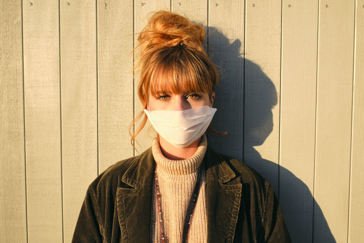 Portrait of woman wearing mask standing against wall