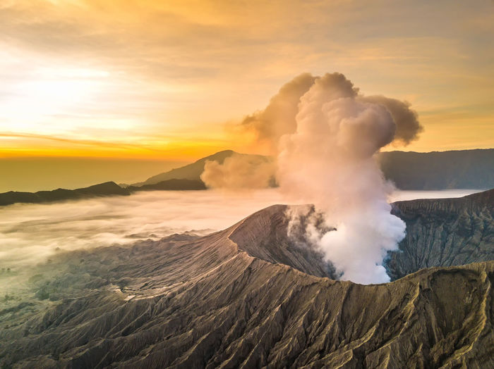 Smoke emitting from volcanic mountain against sky during sunset