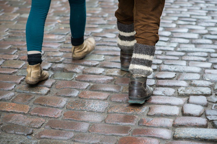 Low section of people walking on cobblestone