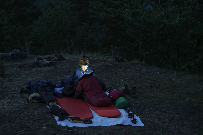 caucasian female hiker reading book/writing journal at night while wildcamping, strong light from headlamp Backpacking Camping Headlamp Hiking Light Reading Travel Trekking Woman Writing Adventure Beam Book Caucasian Clothing Day Evening Female Forest Front View Full Length Hobby Journal Land Leisure Activity Lifestyles Nature Night One Person Outdoors People person Plant Real People Relaxation Sitting Sleeping Sleeping Bag Tree Warm Clothing Winter Young Adult Young Men