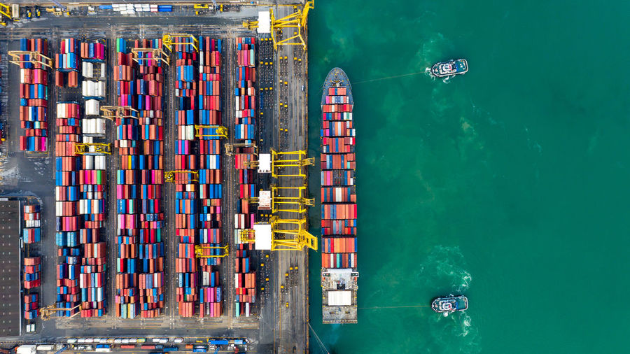 Aerial view tugboats assisting container ship to international commercial dock, global business