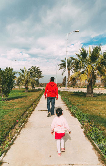 Rear view of father and daughter on palm trees against sky