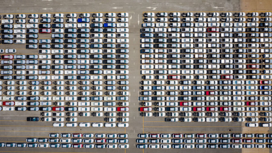 Aerial view of the parked new cars at the automotive plant export sold to dealers