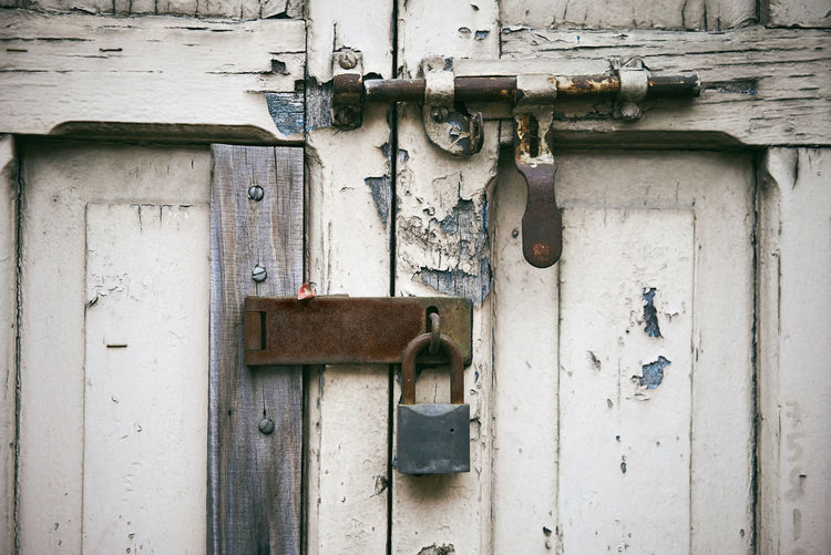 The old aged white wooden door with latch locking with the rustic key lock on the hinge Hinge Home Objects Weathered Aged Close-up Closed Door Entrance Grunge Latch Lock Metal Old Outdoors Protection Rusty Safety Security Solid Stained Steel Texture White Wooden