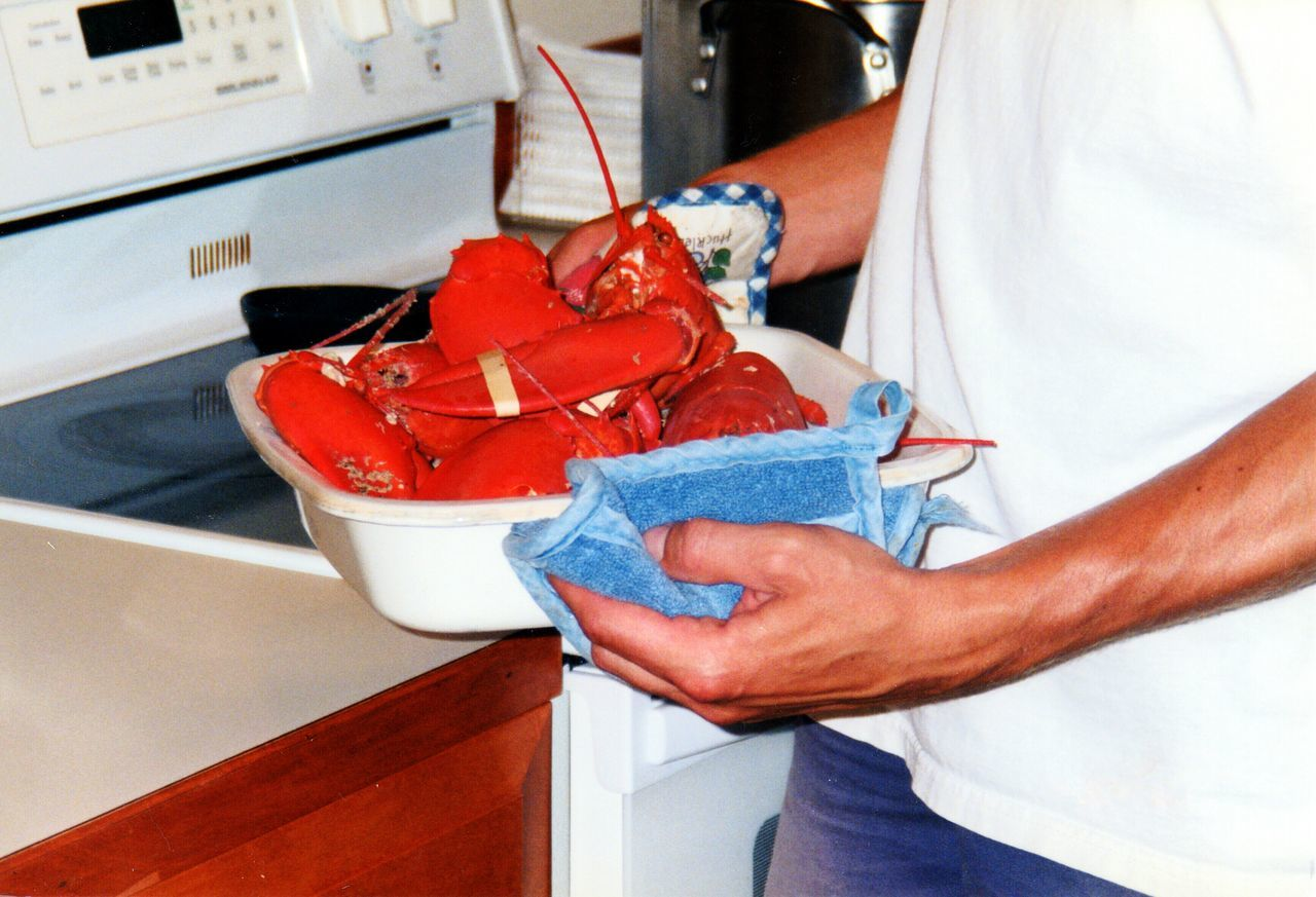 Close-Up Of Man Preparing Seafood In Kitchen