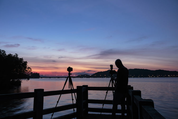Beauty In Nature Camera - Photographic Equipment Day Men Nature Outdoors People Photographing Photography Themes Real People Scenics Sea Silhouette Sky Sunset Technology Tranquil Scene Tranquility Tree Two People Water Women