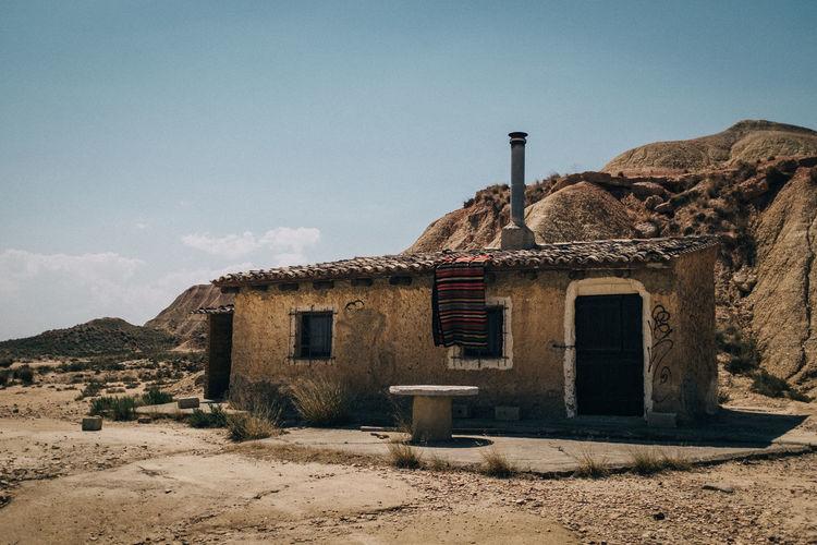 Abandoned built structure on landscape against sky