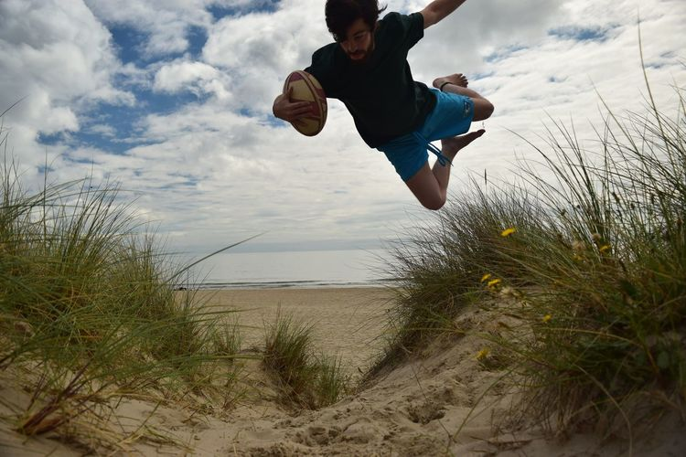 Man with american football jumping over grass at beach against sky