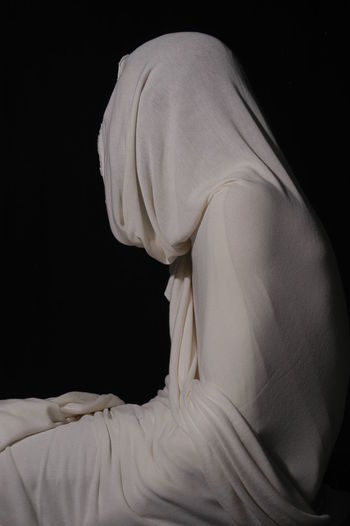 Side view of woman standing against black background