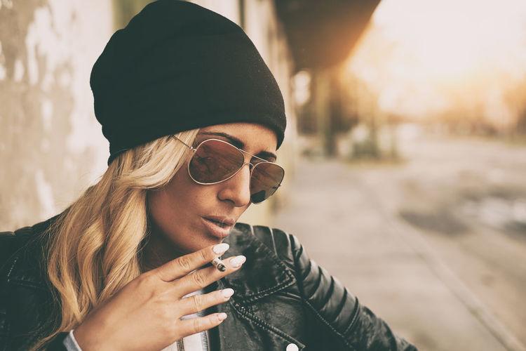 Fashionable young woman wearing jacket smoking cigarette outdoors