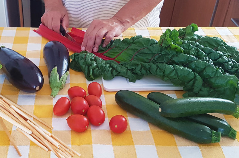 Midsection Of Woman Cutting Vegetable At Table In Kitchen