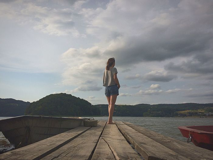 Rear View Full Length Of Woman Standing On Pier Against Lake