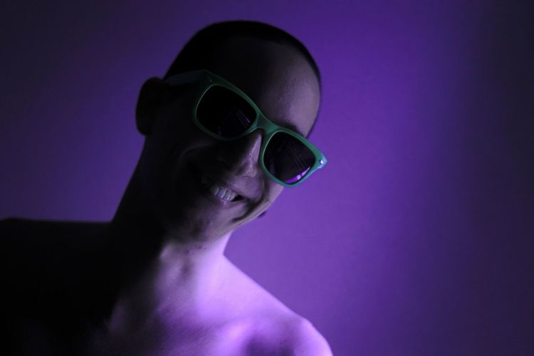 Portrait of young man wearing sunglasses against colored background