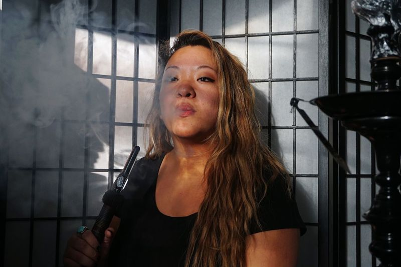 Young woman smoking hookah