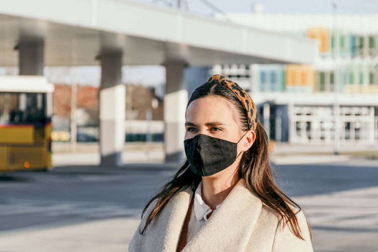 Young woman wearing black face mask in city. walking, confident, covid, corona, epidemic.