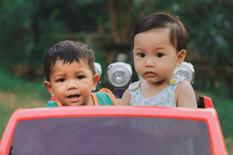 Siblings in toy car