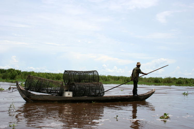 Fisherman oaring boat in lake against sky
