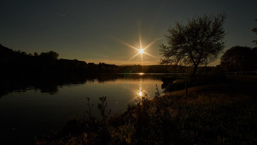 Sunset over river Moselle Reflection Water Sun Sunset Nature Sky Tree Glowing Illuminated Tranquility Sunrays Lake Calm Scenics Beauty In Nature No People Idyllic Tranquil Scene Silhouette Growth Outdoors Day