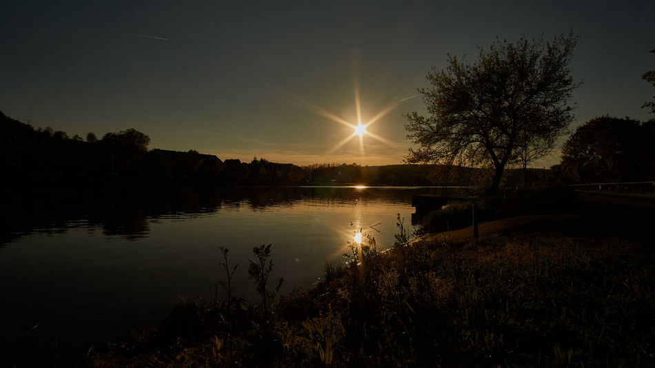 Sunset over river Moselle Beauty In Nature Calm Glowing Idyllic Illuminated Lake Nature No People Reflection Scenics Sky Sun Sunrays Sunset Tranquil Scene Tranquility Tree Water