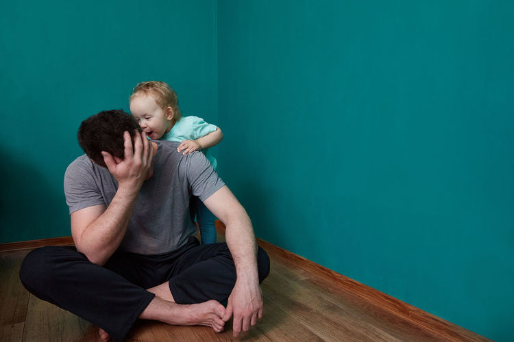 Full length of father with daughter against wall