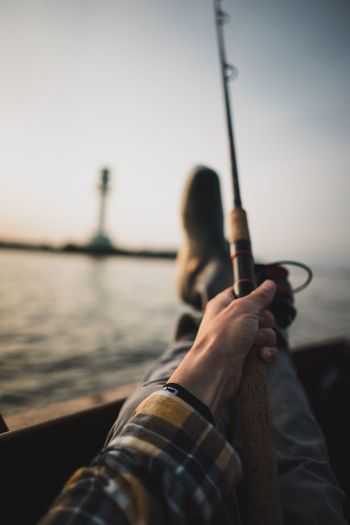 Close-up of man holding fishing rod in boat on sea