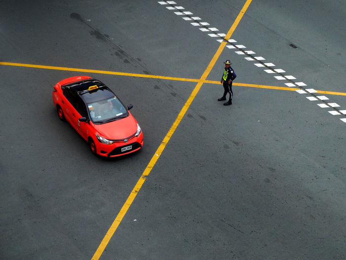 High angle view of traffic cop standing with red taxi on street
