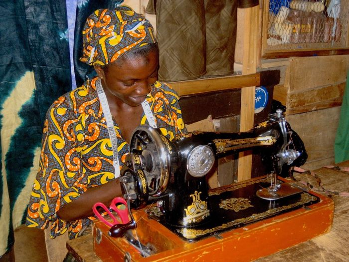 Tailor with tap measure sitting by sewing machine