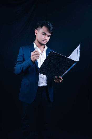 Young businessman reading file while standing against blue background