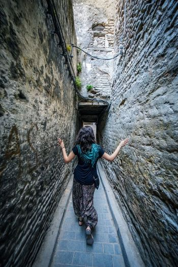 Narrow Fes Morocco Medina Medina De Fez Fes Morocco Ancient Full Length Architecture One Person Motion Climbing Solid Day Rear View Young Adult Rock Rock - Object Hair Outdoors High Angle View Adult Limb Human Arm Built Structure Nature Alley Arms Raised