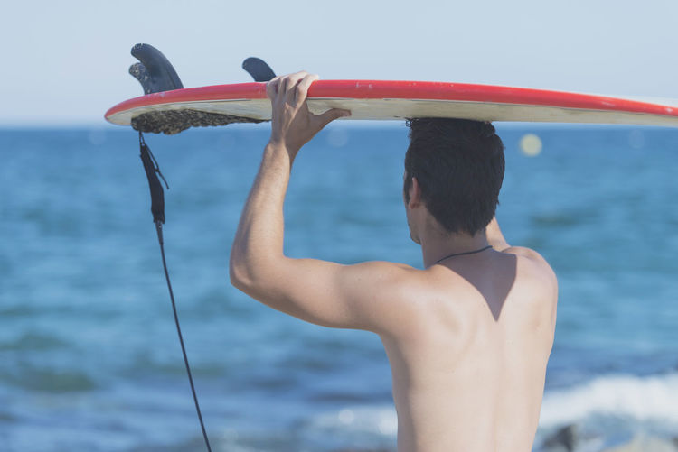 Young attractive surfer holding his surfboard at the beach Alone Fun Lifestyle Man Seashore Surf Surfer Beach Boardwalk Goodvibes Leisure Activity People Real People Sea Sport Sports Summer Sun Sunglasses Surfboard Swimsuit Trendy Vacation Watersports Young Adult