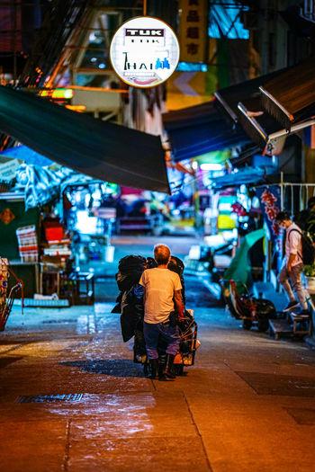 Rear view of people walking on illuminated street at night