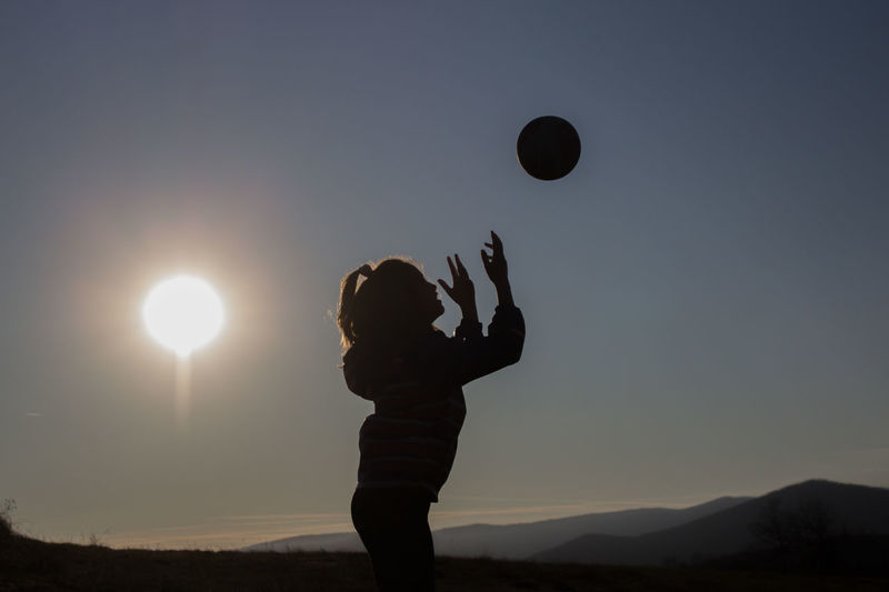 Silhouette little girl playing with ball in background against sky during sunset