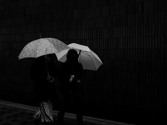 People walking on wet road during rainy season