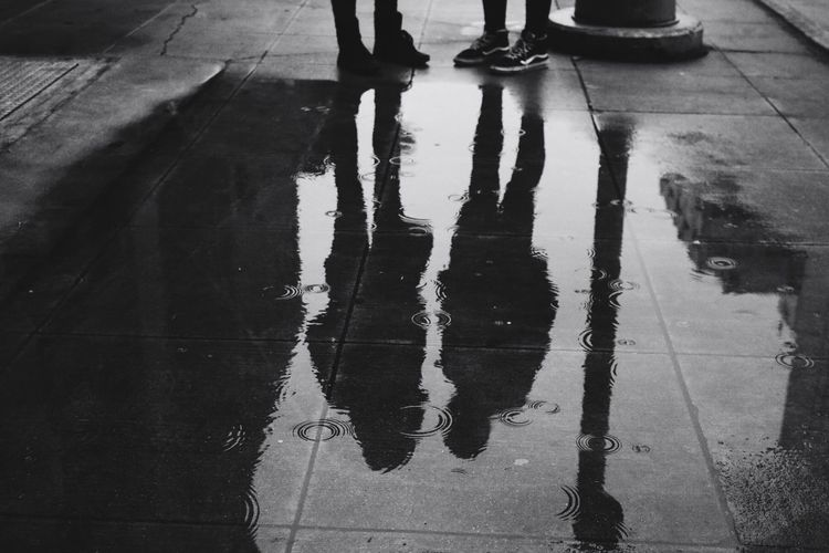 Low section of people standing on wet street during rainy season