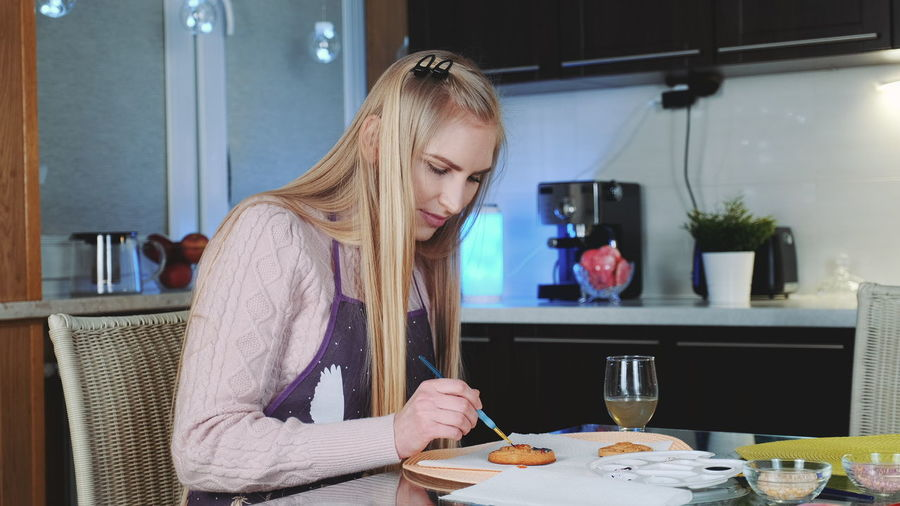 Young woman making christmas cookie on table at home