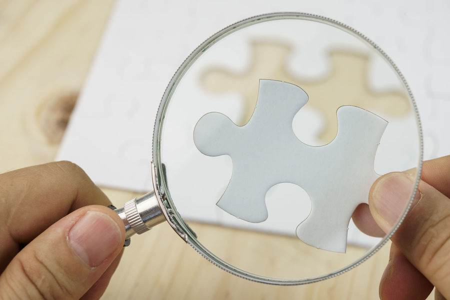 Hand with a magnifying glass inspecting a piece of jigsaw puzzle Checking Close-up Day Holding Human Body Part Human Hand Indoors  Inspecting Magnifying Glass One Person People Personal Perspective Puzzle  Real People Solution