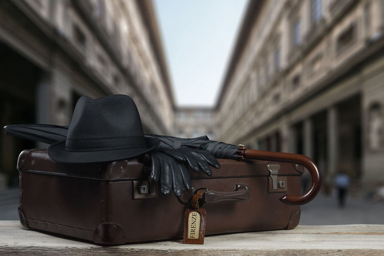 Close-Up Of Suitcase On Table Against Buildings