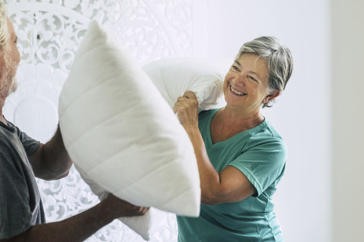 Cheerful Senior Couple Playing Pillow Fight At Home