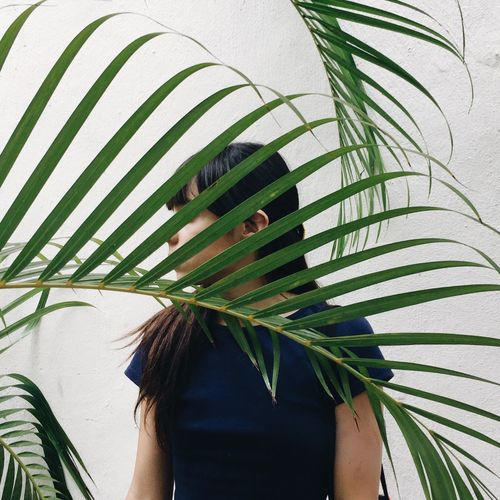 Close-up of young woman behind palm leaves against wall