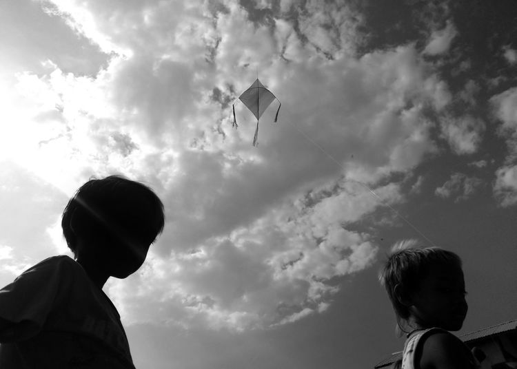 Low angle view of people flying against sky